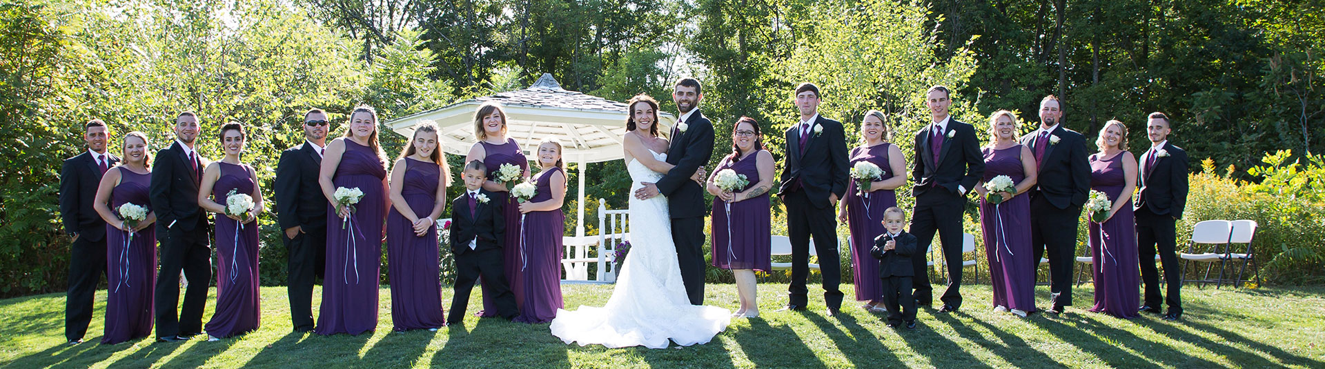 A wedding party poses in front of a gazebo at Catamount Country Club