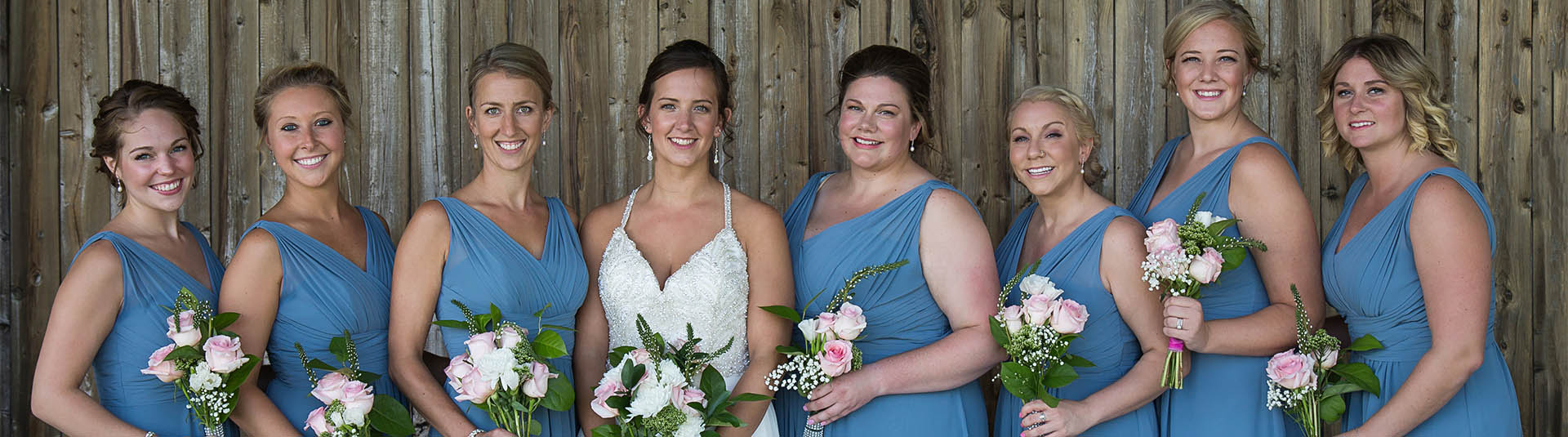 A bride and her bridesmaids pose in front of a fence at Catamount Country Club